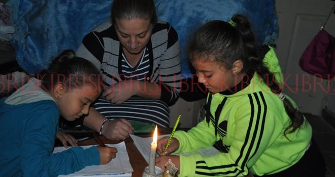 Çocuklar, mum ışığında ders çalışıyor
